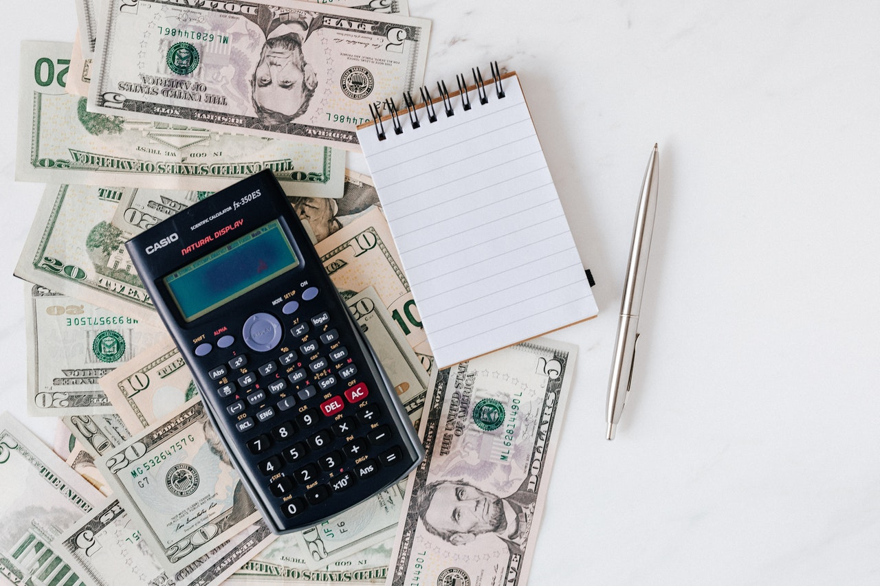 Calculator and notepad on top of dollar bills